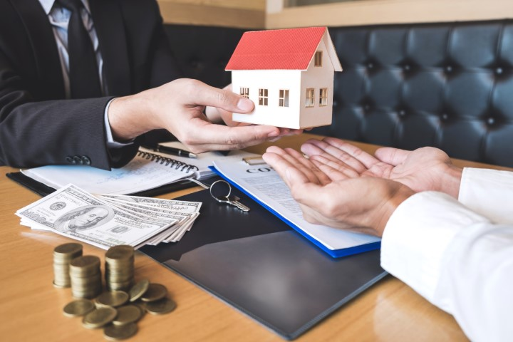 Estate agent sending house model to client after signing agreement contract real estate with approved mortgage application form, concerning mortgage loan offer for and house insurance.